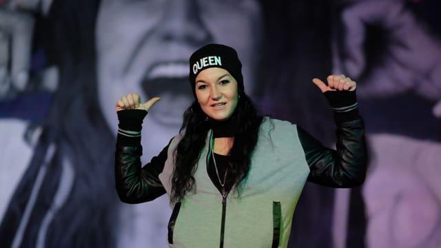 Rapperin posiert vor einem Graffiti von ihr