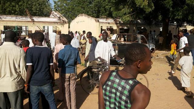 Menschen stehen vor dem zerstörten Schulgebäude in Potiskum