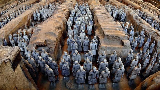Unzählige tönerne bläuliche Soldaten stehen zwischen zwischen grossen Felsen aufgereit.