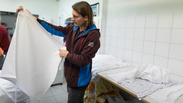 Ein Zivildienstleistender arbeitet in einer Wäscherei.
