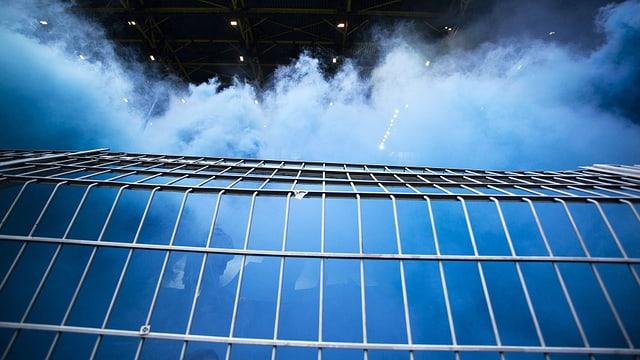 Ein Stadiongitter: dahinter sind Fans und blauer Rauch.