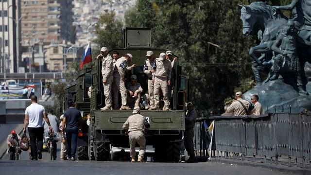 Russische Soldaten auf einem Militärlastwagen neben einem Denkmal.
