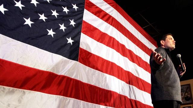 Rubio mit einem Mikrofon in der Hand vor einer riesigen US-Flagge.