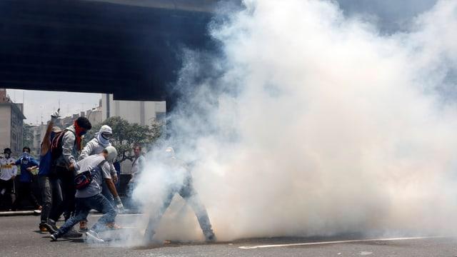 Demonstranten und Polizei, eine Rauchwolke steigt auf