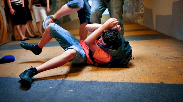Zwei Jugendliche treten in einer für das Foto gestellten Szene auf einen Jugendlichen auf dem Boden ein.