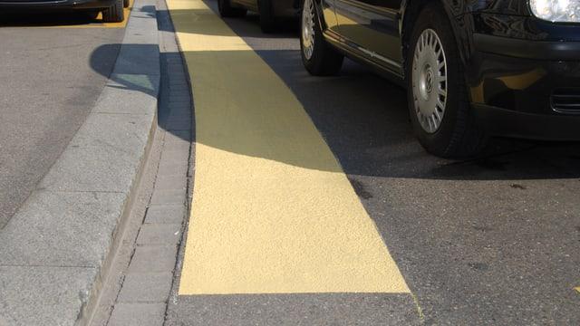 Ein gelber Balken auf der Strassenoberfläche