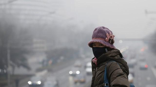 Chinesische Frau mit Mundschutz vor Stadt mit Smog