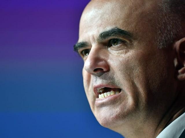 Alain Berset hält eine Rede vor blau-violettem Hintergrund