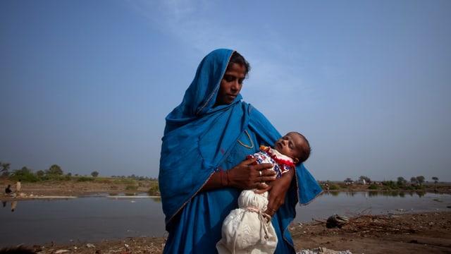 Pakistanische Mutter mit schlafendem Baby auf dem Arm