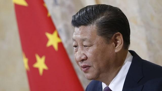 Mann mit Chinaflagge im Hintergrund.