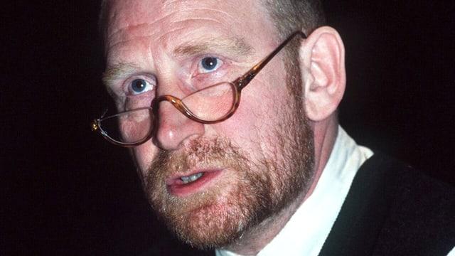 Ein Mann mit Dreitagebart und Brille, die er ganz vorne auf der Nase trägt.