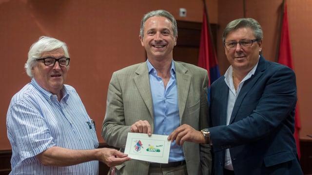 Lega-Präsident Attilio Bignasca, Lega-Ständeratskandidat Battista Ghiggia und SVP-Präsident Gabriele Pinoja halten ein Blatt mit den Logos von Lega und SVP.