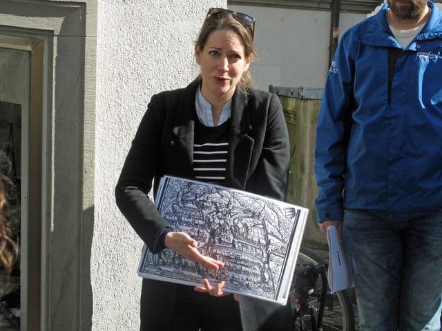 Eine Frau zeigt einen alten Stadtplan.