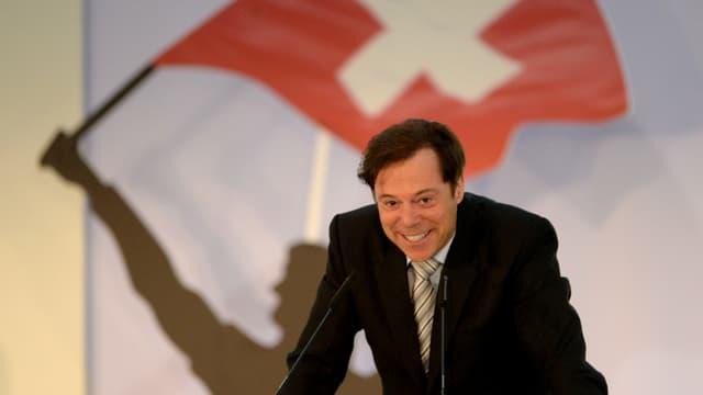 Christoph Mörgeli stützt sich am Rednerpult vor einer Schweizer Fahne auf.