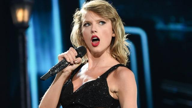 Taylor Swift im schwarzen Oberteil auf der Bühne.