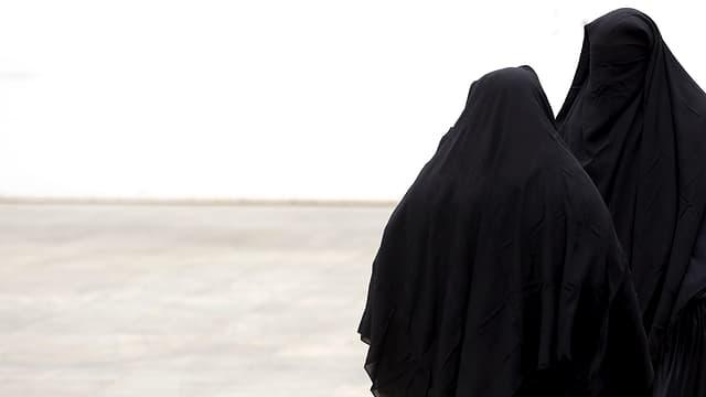 Zwei Burkaträgerinnen vor einer weissen Wand.