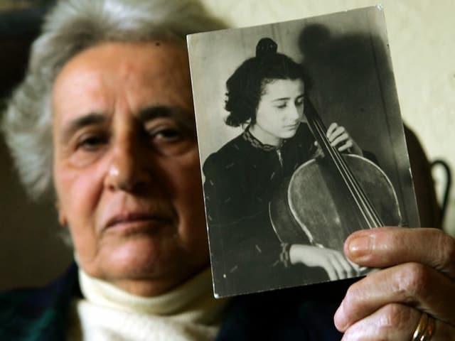 Eine ältere Frau hält ein Schwarzweissbild einer jungen Cellistin in die Kamera.