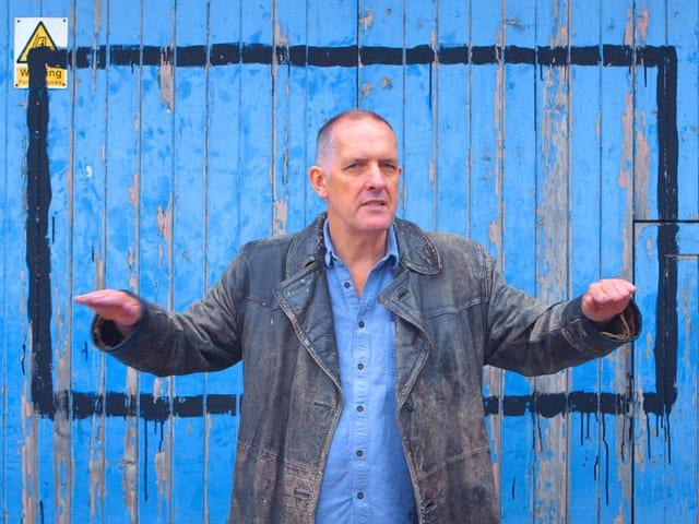 Ein Mann steht vor einer blauen Holzwand.