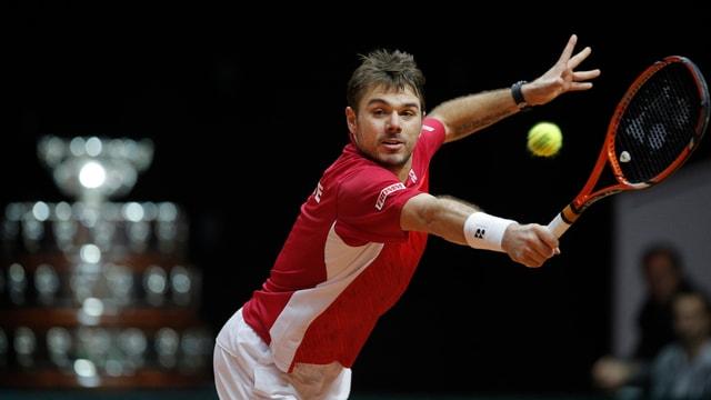 Stan Wawrinka schlägt eine Rückhand, im Hintergrund ist der Davis-Cup-Pokal zu sehen.