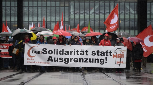 Menschen mit Fahnen und Transparenten laufen vom Basler Messeplatz los.