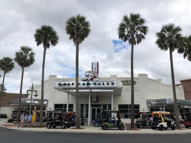 Ein Golfcart-Händler, davor einige Palmen