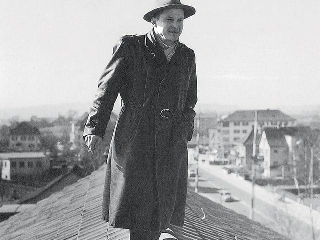 Ein Mann mit Hut und abgewetztem schwarzen Mantel steht auf einem Hausdach.
