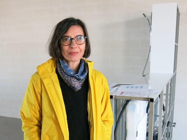 Frau mit gelbem Anorak in einem leerem Raum.