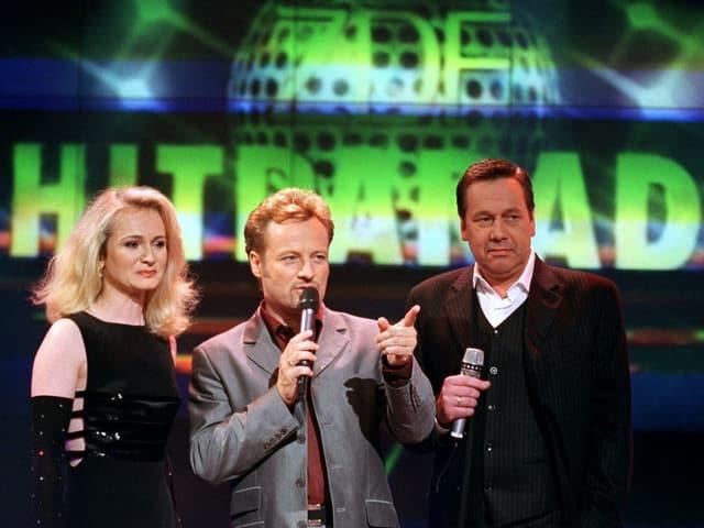 Moderator und zwei Sänger mit traurigem Blick.