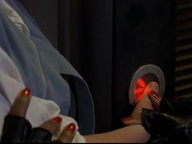 Jemand hält den Finger auf ein Gerät mit runder Scheibe, dahinter leuchtet ein Laser-Strahl.