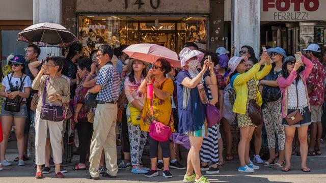 Eine grosse Gruppe von Touristen mit Sonnenschirmen und Handykameras.