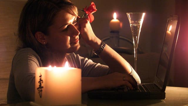 Eine Frau sitz mit Kerzen vor dem Computer