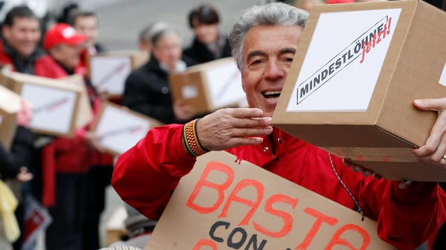 Mann der eine Kiste mit Unterschriften für die Mindestlohn-Initiative übergibt.
