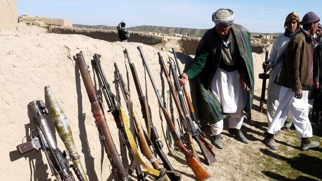 Männer stellen Gewehre an eine Wand.