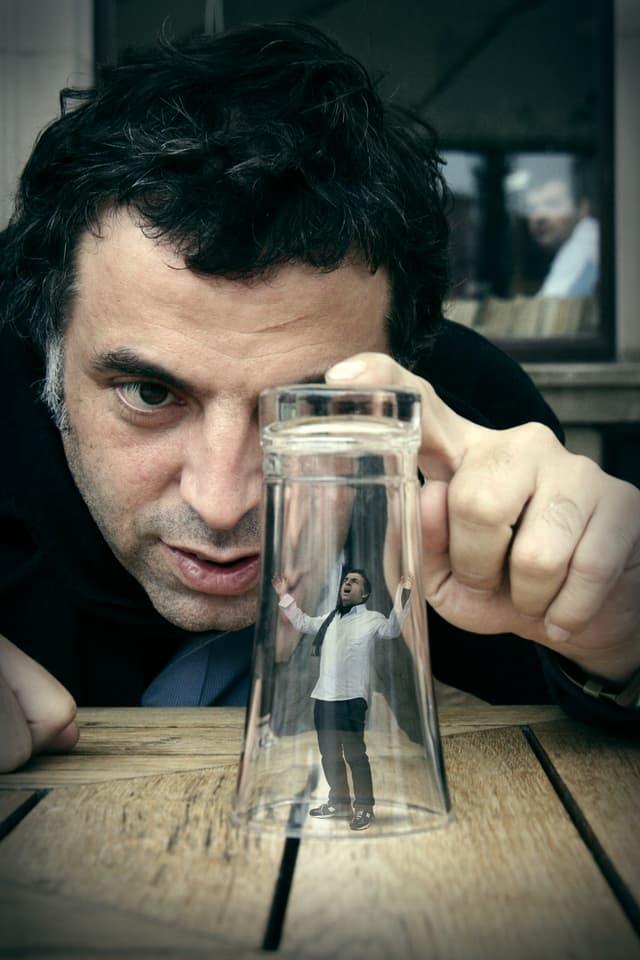 Keret beobachtet sich selber in Miniatur unter einem Wasserglas.
