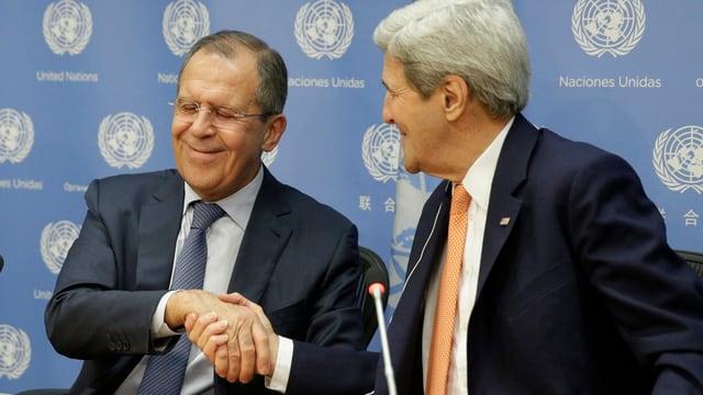 Zwei Männer (Lawrow und Kerry) geben sich die Hand und lächeln.