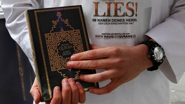 Ein Mann hält einen Koran in der Hand