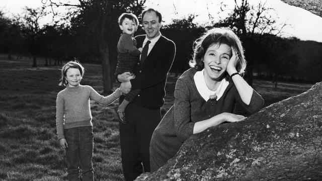 Schwarzweissfoto: Eine Frau lehnt lachend an einem Baumstamm, der auf einer Wiese steht. Hinter ihr steht, ebenfalls lachend, ein Mann. Auf seinem Arm trägt er einen Jungen, an der Hand hält er ein Mädchen.