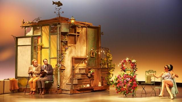 Eine leicht bekleidete Dame ist auf der Bühne. Nebenan steht ein Häuschen mit zwei Männern, die auf einer Bank sitzen.