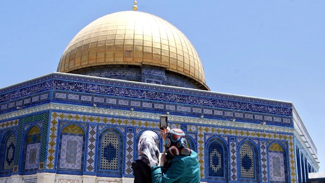 Zwei Frauen mit Kopftuch fotografieren den Felsendom aus der Nähe.