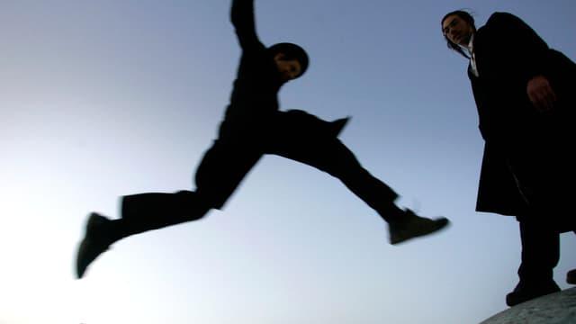 Eine junger Jude im Luftsprung, daneben ein zweiter jüdischer Mann.