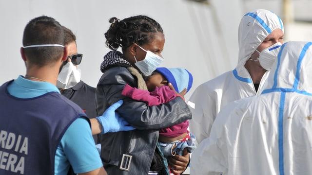 Eine Flüchtlingsfrau mit Kleinkind geht auf Sizilien an Land.