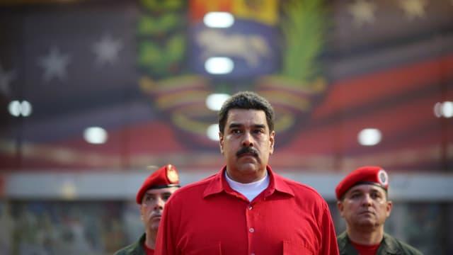 Maduro in rotem Hemd, steht neben zwei Soldaten mit rotem Beret.