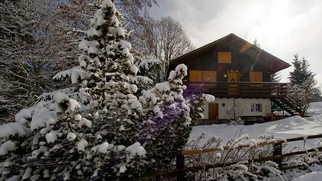 Chalet mit geschlossenen Fensterläden in verschneiter Umgebung.