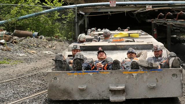 Minenarbeiter liegen auf einem niedrigen Wagen, der in den Bergstollen fährt.