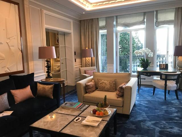 Die suite mit Blick auf den See: Blauer Teppich und Sofa, ein beiger Sessel, und eine silberne Etagere mit Früchten.