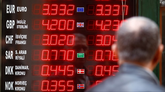 Mann blickt auf Tafel mit Wechselkursen in Istanbul.
