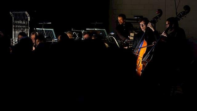 Musikerinnen und Musiker der Sinfonietta. Sie musizieren im Dunkeln.