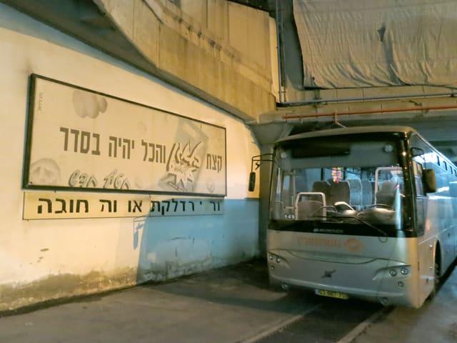 Ein Parkierter Pus neben einem Schild mit hebräsichem Schriftzug.