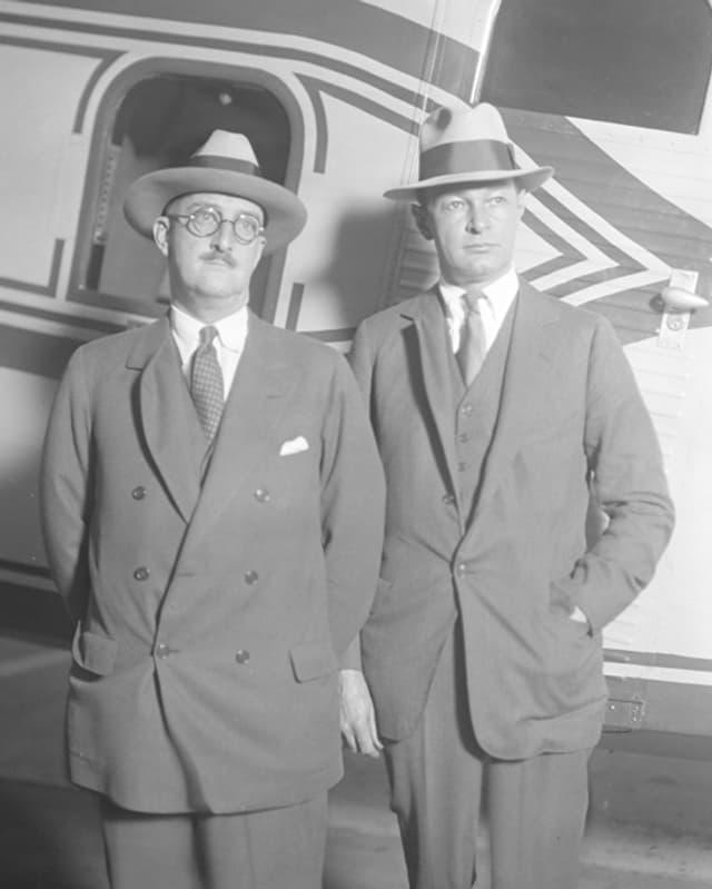 Ein Bild von zwei Männern vor einem Flugzeug.