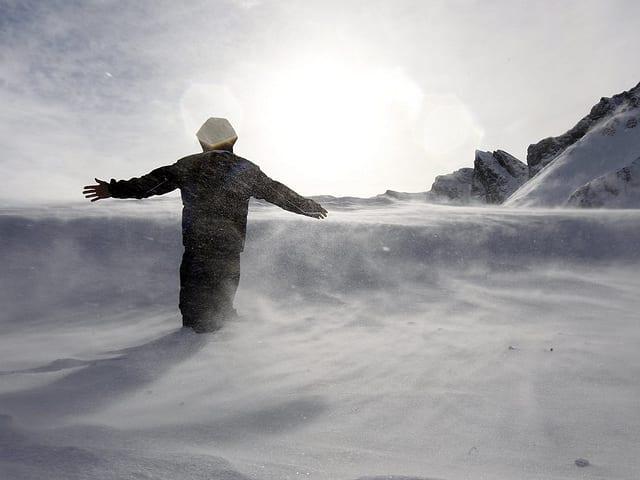 Eine Person steht im Schnee bei stürmischem Wetter